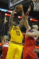 Feb 23, 2014; Cleveland, OH, USA; Cleveland Cavaliers power forward Tristan Thompson (13) drives to the basket against Washington Wizards center Kevin Seraphin (left) and center Marcin Gortat (4) in the third quarter at Quicken Loans Arena. Mandatory Credit: David Richard-USA TODAY Sports