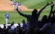 Mar 11, 2014; Surprise, AZ, USA; Fans stretch to catch a ball tossed into the stands by Los Angeles Dodgers second baseman Justin Turner (left) in a game against the Kansas City Royals at Surprise Stadium. Mandatory Credit: Christopher Hanewinckel-USA TODAY Sports