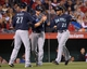 Apr 1, 2014; Anaheim, CA, USA; Seattle Mariners designated hitter Corey Hart (27) congratulates catcher John Buck (4) and second baseman Robinson Cano (22) after they scored in the third inning against the Los Angeles Angels at Angel Stadium of Anaheim. Mandatory Credit: Kirby Lee-USA TODAY Sports