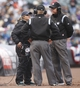 Apr 6, 2014; Denver, CO, USA; Umpires Mike Winter (right) and Mike Muchlinski (center) confer during a reply during the first inning between the Colorado Rockies and the Arizona Diamondbacks at Coors Field. Mandatory Credit: Chris Humphreys-USA TODAY Sports