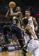 Apr 9, 2014; Milwaukee, WI, USA; Indiana Pacers guard Donald Sloan (15) shoots the ball between Milwaukee Bucks guard Brandon Knight (11) and center Zaza Pachulia (27) during the third quarter at BMO Harris Bradley Center. Mandatory Credit: Jeff Hanisch-USA TODAY Sports