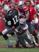Apr 12, 2014; Columbus, OH, USA; Ohio State Scarlet Team quarterback Cardale Jones (12) is tackled by Ohio State Gray Team defensive end Tyquan Lewis (59) during the Ohio State Buckeyes Spring Game at Ohio Stadium. Mandatory Credit: Greg Bartram-USA TODAY Sports