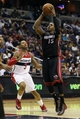 Apr 14, 2014; Washington, DC, USA; Miami Heat guard Mario Chalmers (15) shoots the ball as Washington Wizards guard Bradley Beal (3) looks on in the fourth quarter at Verizon Center. The Wizards won 114-93. Mandatory Credit: Geoff Burke-USA TODAY Sports