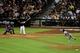 Apr 15, 2014; Phoenix, AZ, USA; Arizona Diamondbacks first baseman Paul Goldschmidt hits a single off of New York Mets starting pitcher Jenrry Mejia (right) as catcher Travis d'Arnaud (left) watches during the fourth inning at Chase Field. Mandatory Credit: Matt Kartozian-USA TODAY Sports