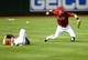 Apr 30, 2014; Phoenix, AZ, USA; Arizona Diamondbacks shortstop Cliff Pennington (right) throws to second base as outfielder Cody Ross lays on the ground in the tenth inning against the Colorado Rockies at Chase Field. Mandatory Credit: Mark J. Rebilas-USA TODAY Sports
