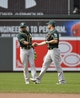 Jun 8, 2014; Baltimore, MD, USA; Oakland Athletics outfielders Yoenis Cespedes (left) and Craig Gentry (right) shake hands after a game against the Baltimore Orioles at Oriole Park at Camden Yards. The Athletics defeated the Orioles 11-1. Mandatory Credit: Joy R. Absalon-USA TODAY Sports