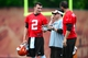 Jun 12, 2014; Berea, OH, USA; Cleveland Browns Johnny Manziel (left) talks with quarterbacks coach Dowell Loggains and Tyler Thigpen during minicamp at Browns training facility. Mandatory Credit: Andrew Weber-USA TODAY Sports