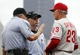 Jul 6, 2014; Pittsburgh, PA, USA; MLB umpires Dale Scott (5) and Dan Iassogna (middle) talk with Philadelphia Phillies concerning a replay against the Pittsburgh Pirates during the eighth inning at PNC Park. The Pirates won 6-2. Mandatory Credit: Charles LeClaire-USA TODAY Sports
