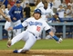 Jul 30, 2014; Los Angeles, CA, USA; Los Angeles Dodgers infielder Justin Turner (10) slides into home plate to score the winning run in the 10th inning against the Atlanta Braves at Dodger Stadium. The Dodgers defeated the Braves 2-1 in 10 innings. Mandatory Credit: Kirby Lee-USA TODAY Sports