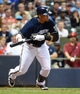 Aug 5, 2014; Milwaukee, WI, USA;  Milwaukee Brewers center fielder Carlos Gomez (27) drives in a run with a bunt single in the fifth inning against the San Francisco Giants at Miller Park. Mandatory Credit: Benny Sieu-USA TODAY Sports